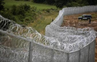 Bulgarian border police stand near a barbed wire fence on the Bulgarian-Turkish border